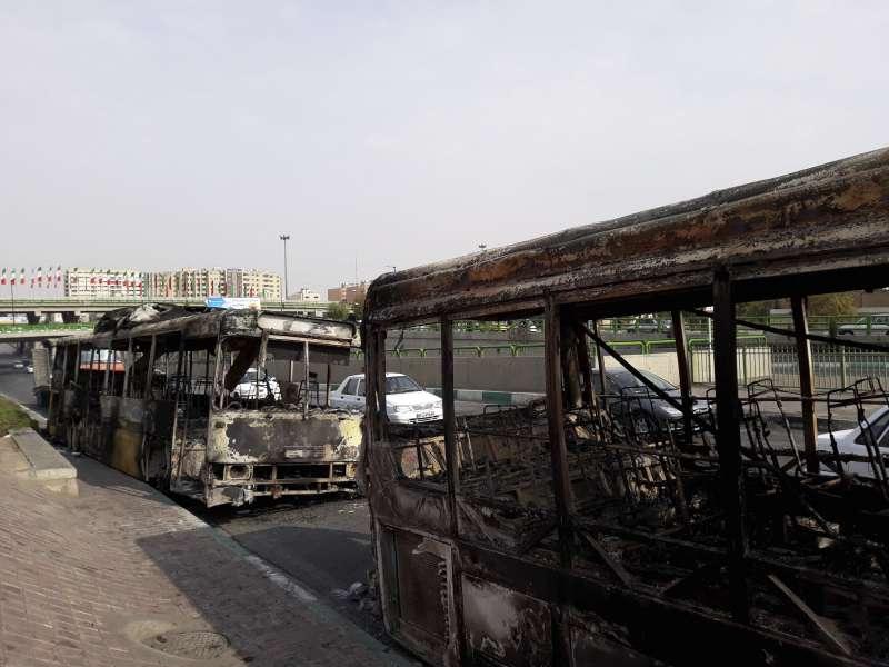 伊朗政府宣布調漲油價,在全國各地引爆激烈抗議,公車亦遭示威者焚毀。(AP)