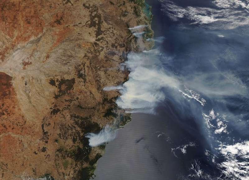 衛星照片顯示,新南威爾斯山區野火的濃煙隨著強風襲向東南方。(美聯社)