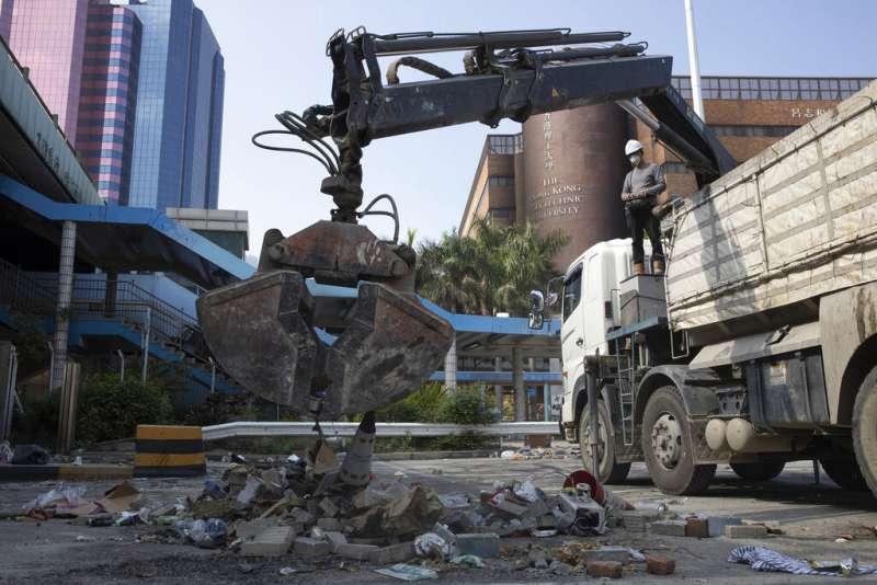 2019年11月20日在香港香港理工大學外,有工人操作大型器具移除路障。(AP)