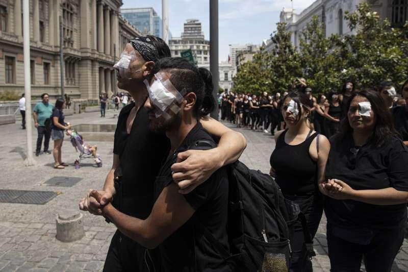智利示威者貼上眼罩,抗議警方鎮暴濫用武力。智利示威持續一個多月來,已有220餘人在鎮壓中失明。(AP)