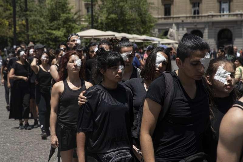 智利示威遭警方鎮壓,至少220人被攻擊而失明。圖為民眾貼上眼罩,抗議警方濫用暴力。(AP)