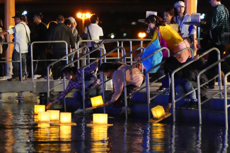 參加者把自己的心願或給已逝親友的寄語寫在水燈上,然後施放到水面。(圖/風傳媒攝)