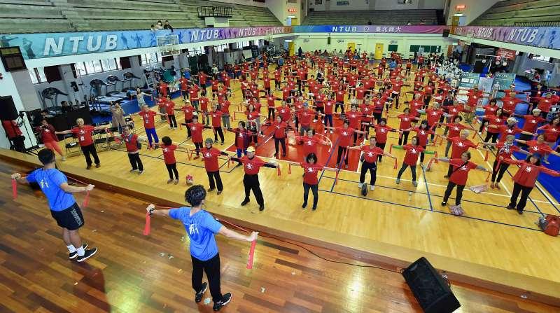 BEING fit新世代健身房教練團隊帶領全體熟齡使用彈力帶,透過簡單的動作就可鍛鍊肌力。(圖/千禧之愛健康基金會提供)