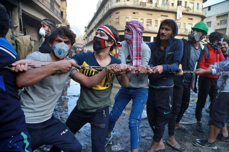 伊拉克爆發大規模示威,民眾呼籲團結一心,終結深化族群分裂的「配額制度」。(AP)