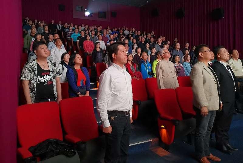 《祭旗》高雄首場特映會,觀眾隨劇中人主動起立唱國歌。(作者提供)