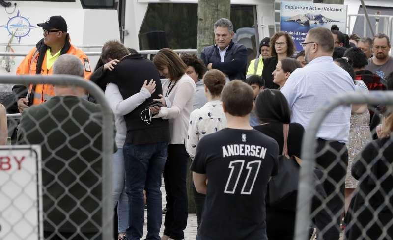 紐西蘭白島火山爆發慘劇,當局找回6位失蹤者遺體,其餘2位疑似掉入海中仍在搜索,圖為岸上等待的傷痛家屬。(AP)