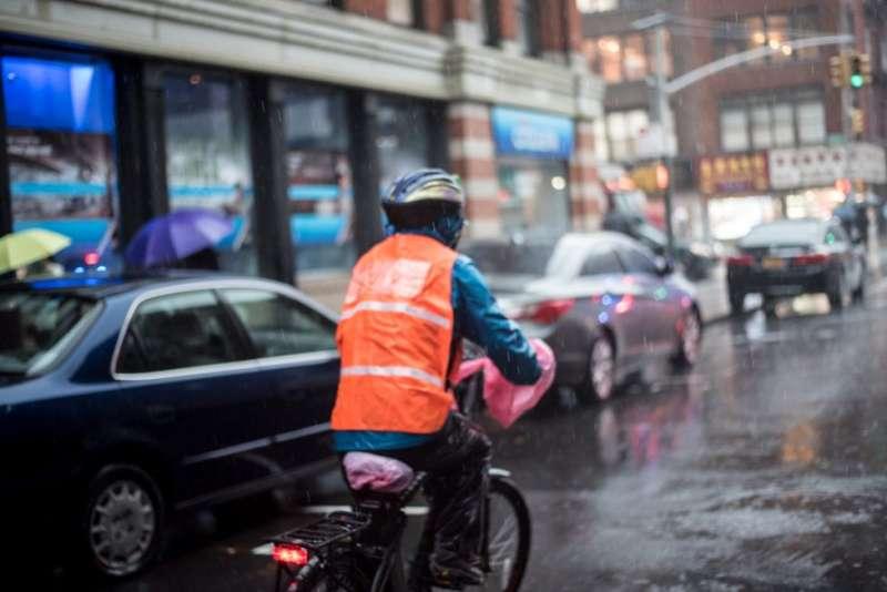 冒雨送餐的李蒙芭。(圖/BBC News。攝影:Katie Salisbury朱潔琳)