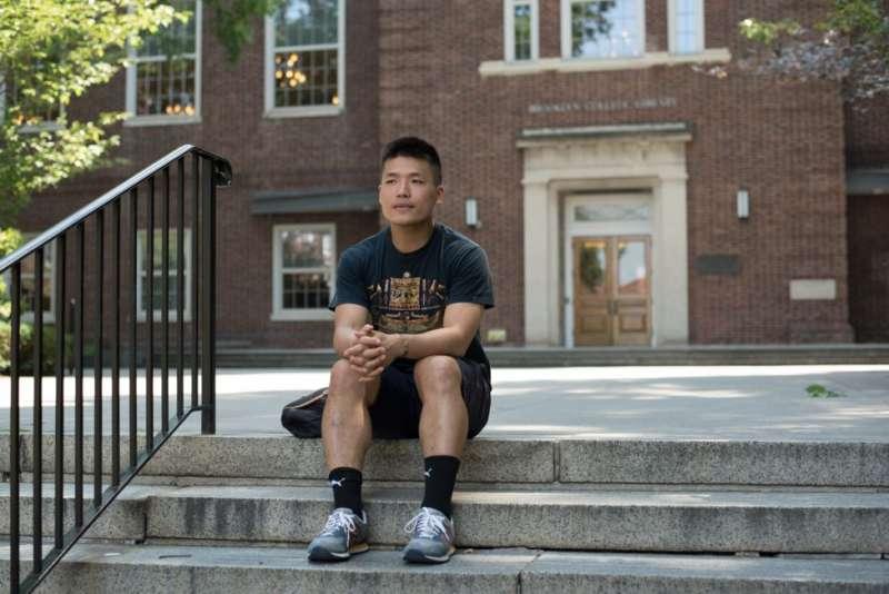 陳曉登坐在布魯克林學院前的階梯上,他剛從這所學校獲得政治學學位。(圖/BBC News。攝影:Katie Salisbury朱潔琳)