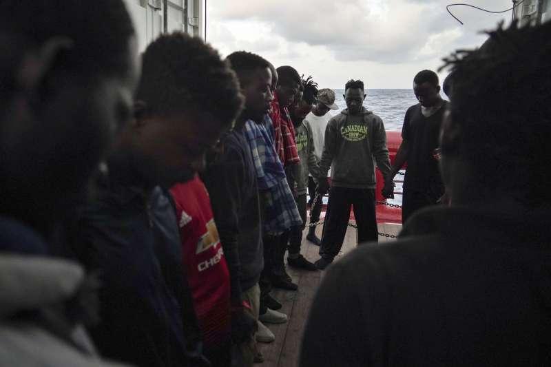利比亞發難民財。一群海上難民正在牽手祈禱,希望成功抵達歐洲並獲得庇護。(AP)