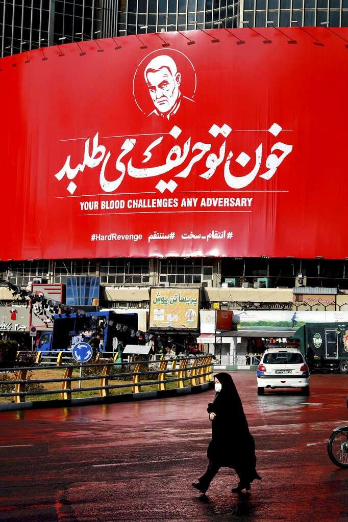 一名伊朗婦人走過德黑蘭的街頭,背後是遭到美軍空襲炸死的蘇萊曼尼肖像。(美聯社)