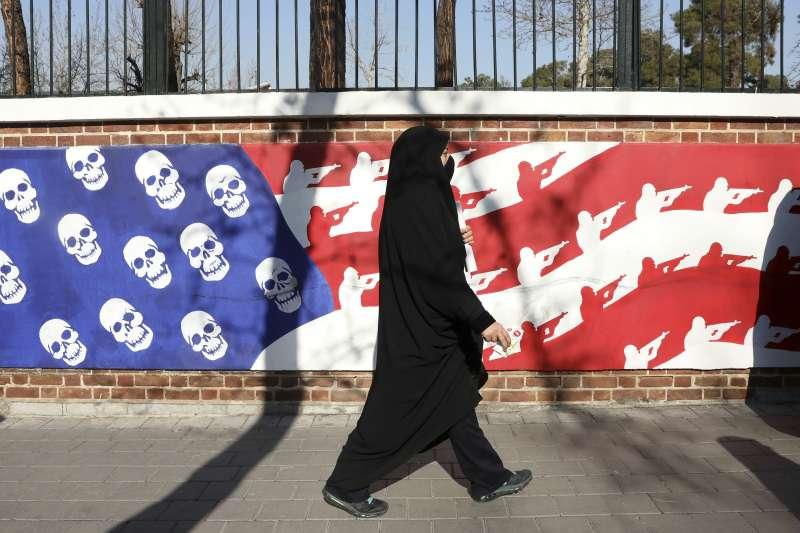 伊朗民眾上街哀悼「聖城軍」司令蘇萊曼尼的死,圖為美國國旗被畫上骷顱頭與軍隊圖像。(AP)