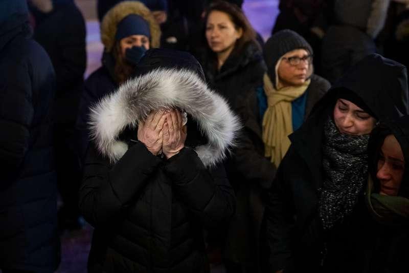 2020年1月8日,一架從伊朗德黑蘭起飛的波音737客機失事,共176人罹難,親友掩面哀悼。(AP)