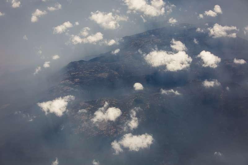 圖為新南威爾斯南部山區,火勢造成的厚重霧霾底下隱約可見野火肆虐痕跡。(美聯社)