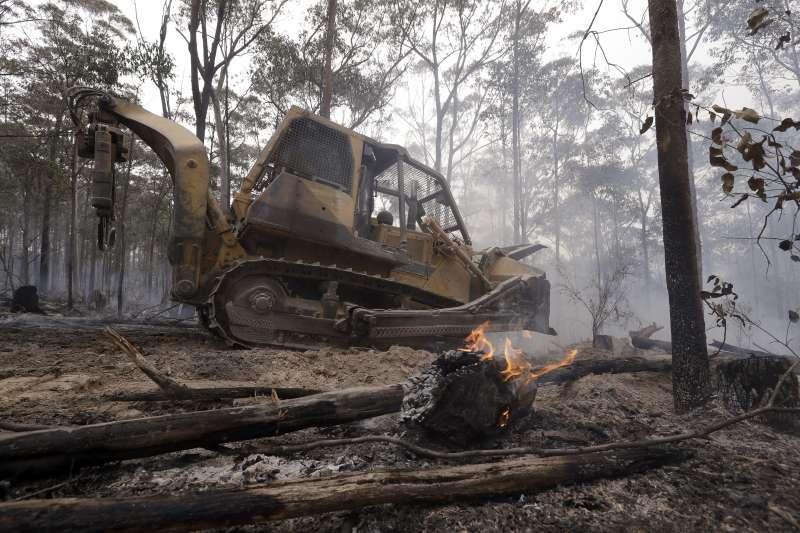 除了消防車,澳洲政府也投入堆土機控制火勢。(美聯社)