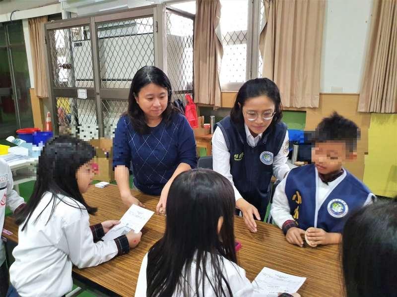移民官蔡宜君(右二)教學童幫助外國人來臺申請外僑居留證。(左2為明德國小教務主任蔡雅芬) (圖/內政部移民署提供)