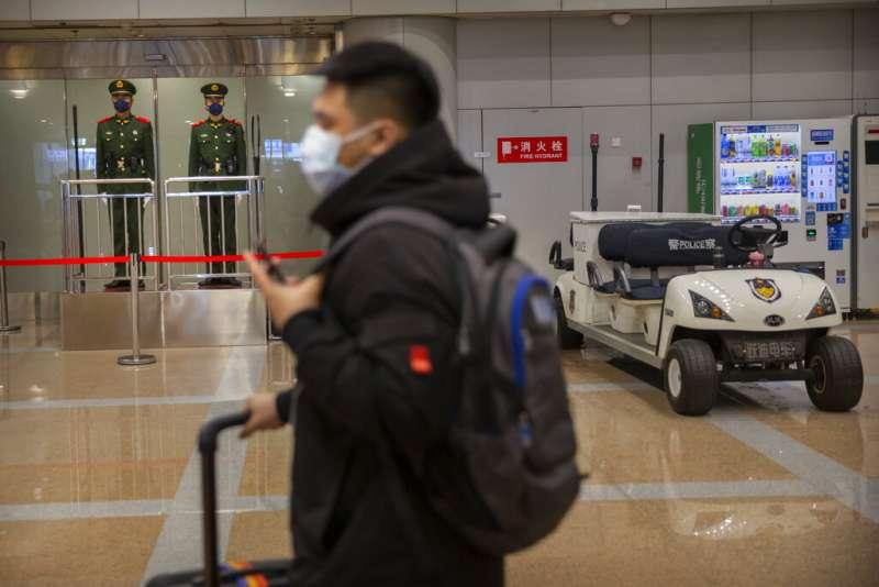 武漢肺炎疫情不斷升高,北京首都機場的旅客也紛紛戴起口罩。(美聯社)