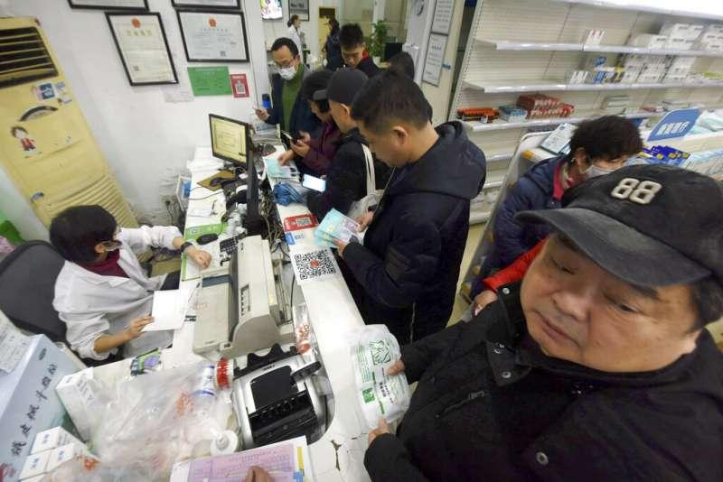 武漢肺炎疫情不斷升高,浙江杭州的民眾為了買口罩必須排隊結帳。(美聯社)