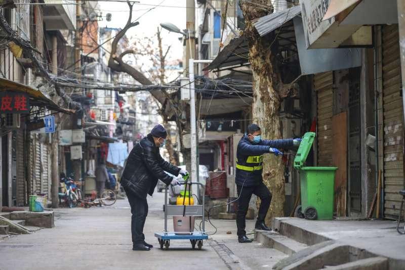 武漢肺炎疫情蔓延,中國當局派員在武漢街頭加強消毒工作。(美聯社)