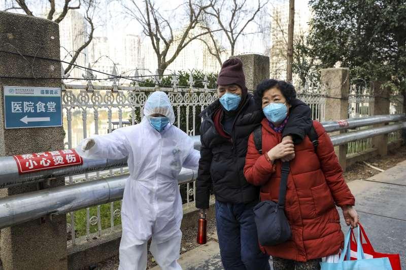 武漢肺炎疫情持續擴大,當地醫護人員全副武裝接待病患家屬(AP)