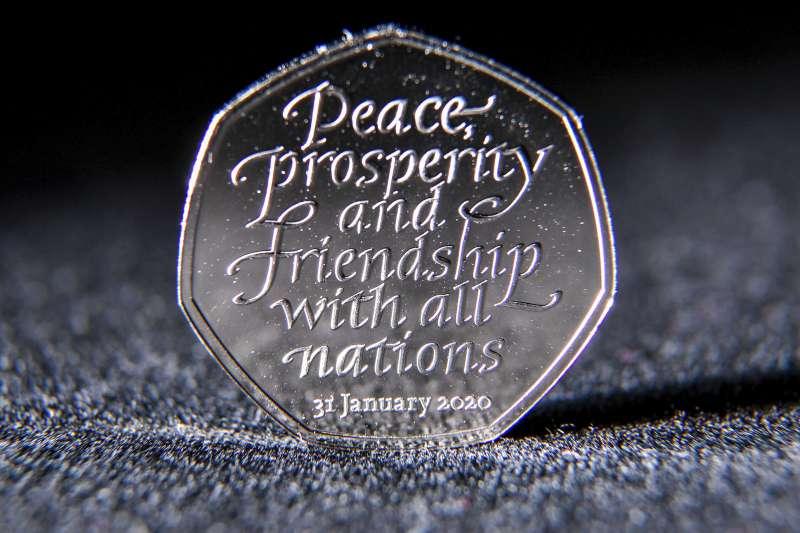 英國脫歐。英國發行面額50便士的「脫歐紀念幣」,印有字樣「願所有國家擁有和平、繁榮與友誼」。(AP)