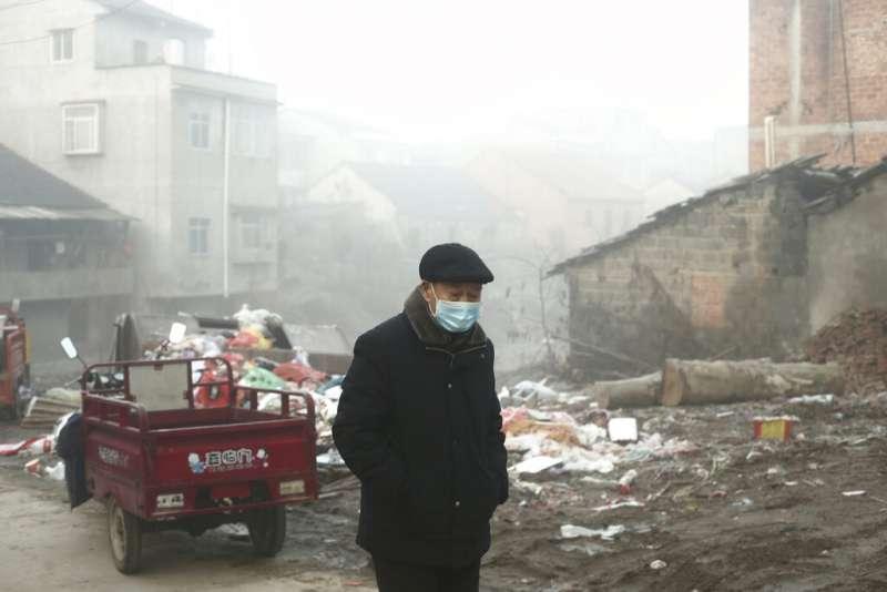 武漢肺炎疫情升高,湖北的街頭顯得人煙稀少,街上民眾也紛紛戴起口罩。(美聯社)