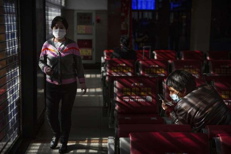 武漢肺炎疫情持續蔓延,北京火車站內的旅客配戴口罩(AP)