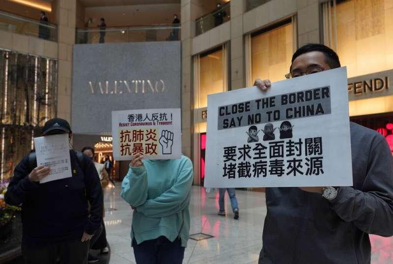 武漢肺炎疫情肆虐,每日有大量中國旅客進入的香港至今未能全面封關,多位香港民眾手持標語抗議。(美聯社)