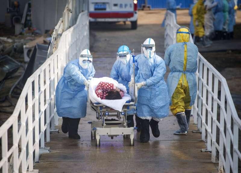 武漢的醫護人員正在將病患送往火神山醫院。(美聯社)