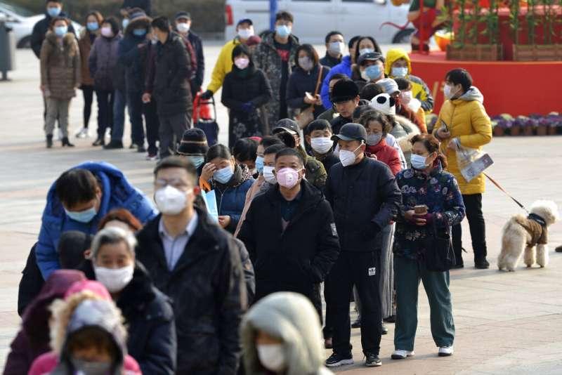 武漢肺炎疫情肆虐,南京市4日晚間發布公告全面實行「小區封閉管理」。圖為南京民眾正在排隊搶購口罩。(美聯社)