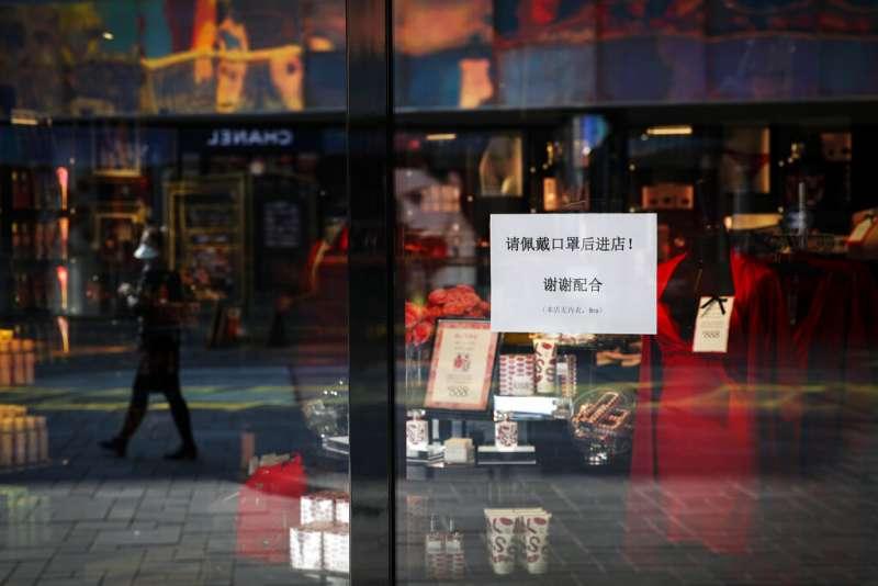 武漢肺炎疫情肆虐,北京商家掛起了「進入請戴口罩」的告示。(美聯社)