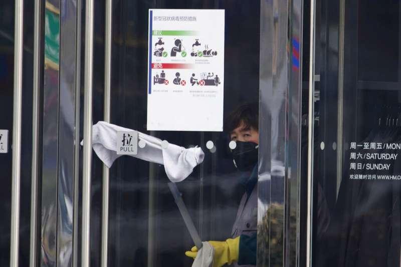 北京一處大樓入口張貼著武漢肺炎疫情的注意事項。(美聯社)
