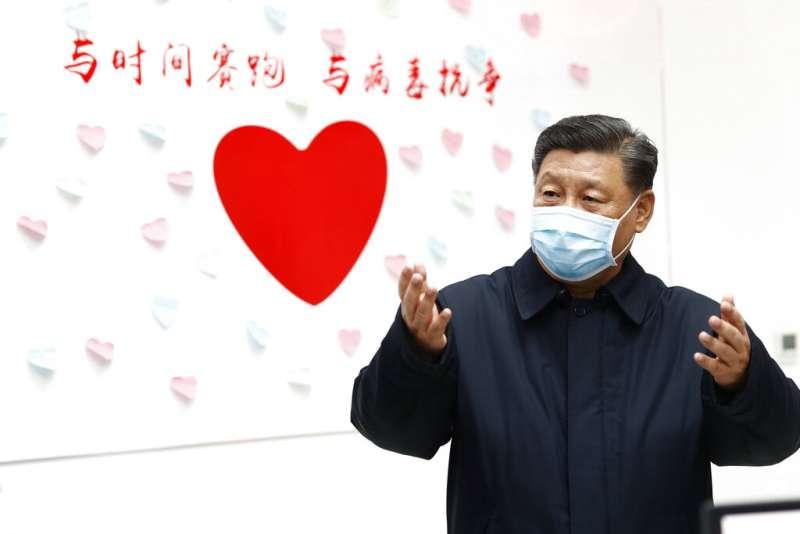 新華社發布一張的習近平照片,背後的牆上還寫著「與時間賽跑,與病毒抗爭」。(美聯社)
