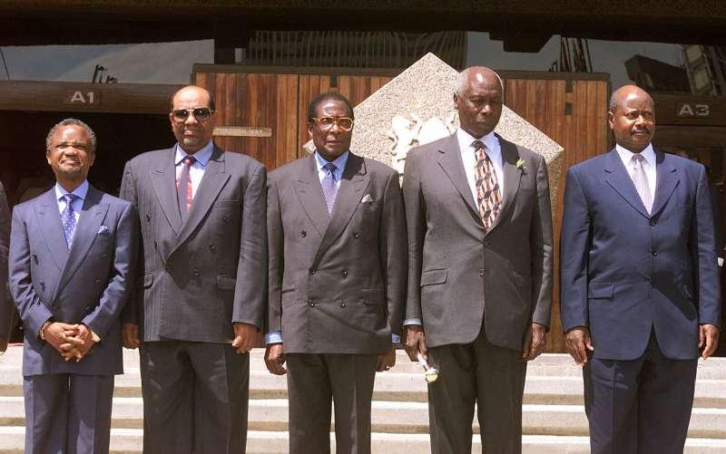 1999年,前蘇丹獨裁總統巴希爾(左二)向支持者揮手致意。他在2019年4月遭政變下台,如今將因戰爭罪被送往國際刑事法院審判。