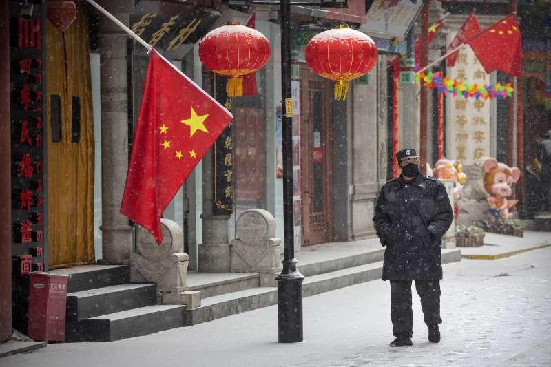 武漢肺炎。2月5日,北京一名維安人員戴著口罩在雪中巡邏。(AP)