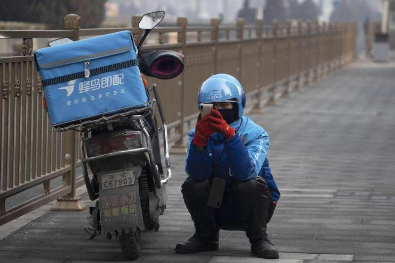 新冠肺炎、武漢肺炎。肺炎疫情影衝擊中國各行各業,圖為一名外送員在路邊等候接單。(AP)