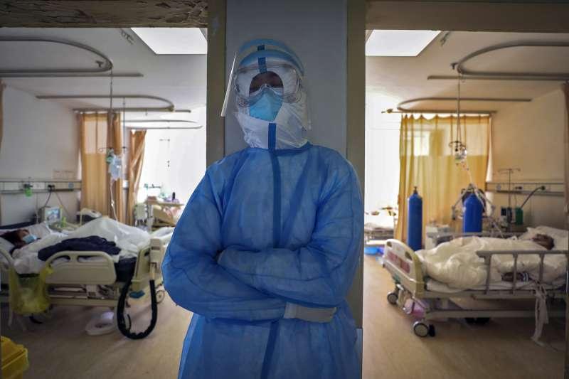 中國湖北省武漢市,身著全套保護裝束的醫護人員只能趁隙站著打瞌睡。新冠肺炎、武漢肺炎。(AP)