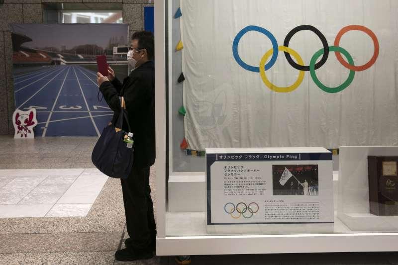 日本東京,一名戴口罩的男子站在奧運標誌旁。受新冠肺炎疫情影響,2020年東京奧運能否舉辦成未知數。(AP)