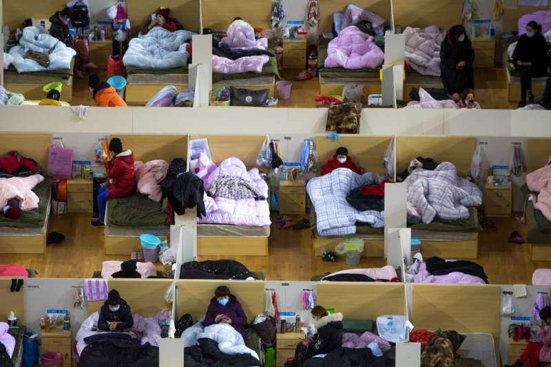 被安置在武漢體育館裡的武漢肺炎病患。(美聯社)