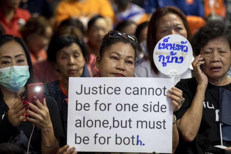 泰國未來前進黨倡遭法院判決解散且10年不得參政,支持者舉著標語批評司法不公。(AP)