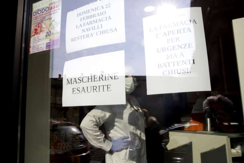 義大利北部倫巴底大區科多諾的藥局窗戶上貼著標語「口罩已售完」(美聯社)