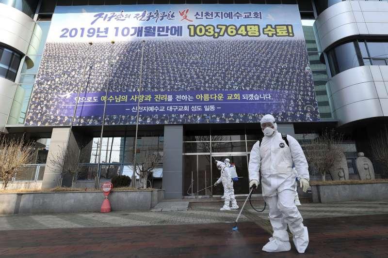 2月20日,全身穿著防護裝備的工作人員在南韓大邱新天地教會建築物進行消毒(美聯社)