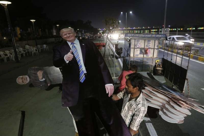 美國總統川普24日訪問印度,展開2天的國是訪問,印度工人正在準備川普的人形立牌(美聯社)