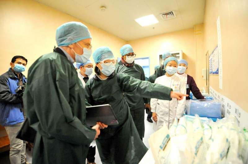 世界衛生組織(WHO)派往中國的專家團隊,24日被指進入武漢醫院考察疫情後,未遵守隔離檢疫14天的規定,就搭機離開中國。圖為專家組組長艾沃德(左2)23日率團進入同濟醫院光谷院區考察。(中新社)