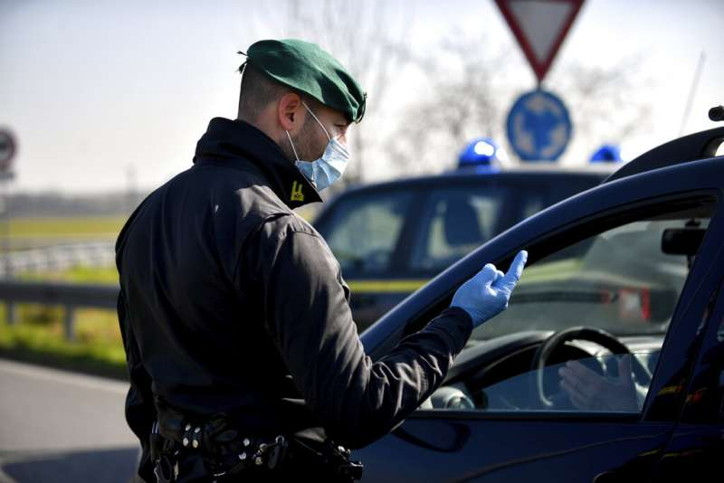 義大利部分地區採取封城措施後,便有戴著口罩的警察在檢查點管制進出。(美聯社)