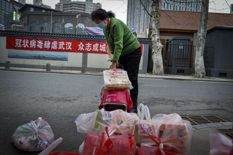 中國武漢肺炎(新冠肺炎)疫情持續延燒,武漢民眾拿取志工分配的食物(AP)