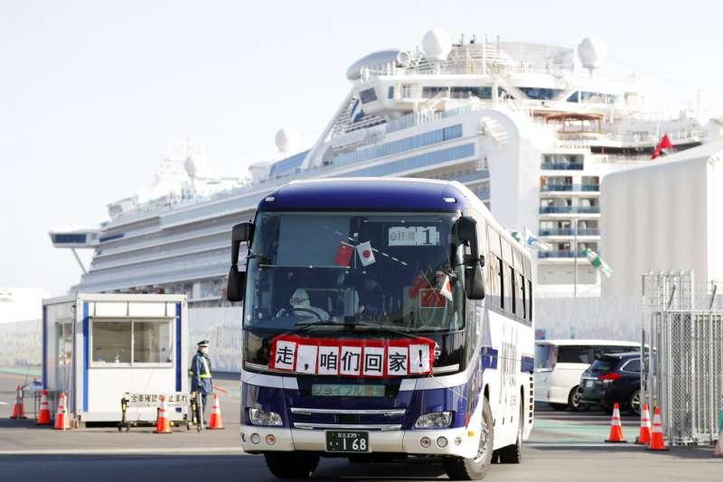 載運「鑽石公主號」香港乘客離開橫濱港的巴士,車前掛起了「走,咱們回家!」的布條。(美聯社)