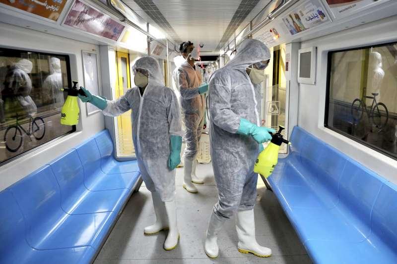 武漢肺炎(新冠肺炎)疫情在伊朗快速爆發,圖為伊朗清潔人員消毒大眾運輸工具。(AP)