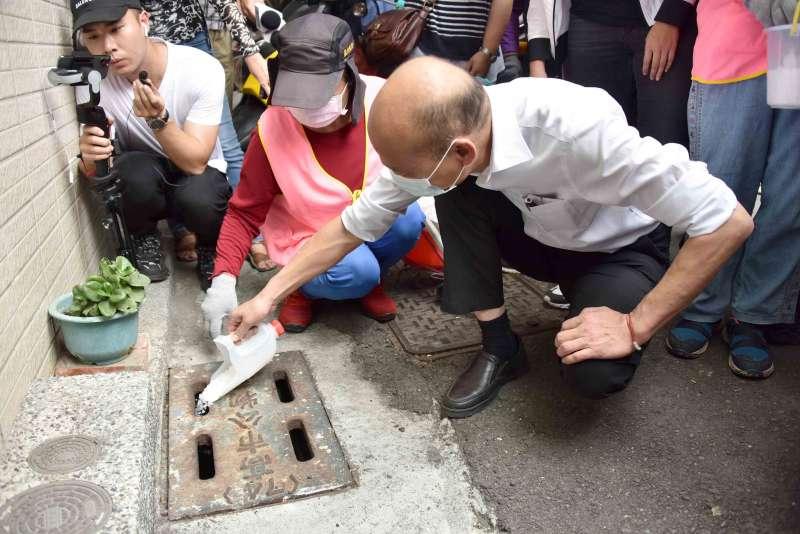 韓國瑜也在志工媽媽的引導下,沿路針對有陽性反應的水溝投放鹽巴,與當地民眾一同攜手防治登革熱。(圖/徐炳文攝)