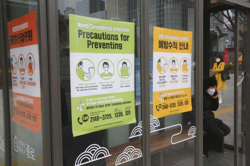 武漢肺炎疫情肆虐,南韓首爾街頭許多地方都有加強防疫的宣傳海報。(美聯社)