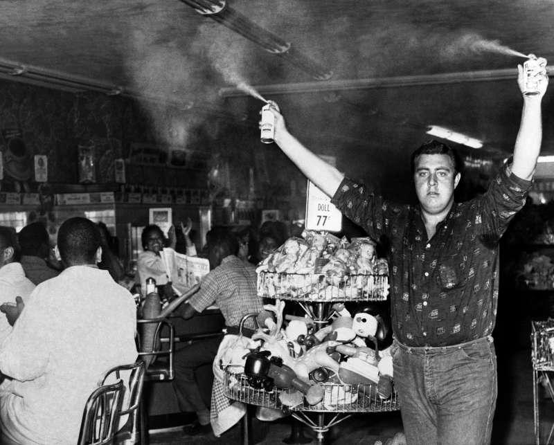 1960年10月,亞特蘭大黑人學生在商店內靜坐時遭一名21歲白人男子噴灑驅蟲劑。(AP)